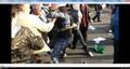 Невидимый человек бьет ногой по шлему Троерина, шлем перекатывается через руки людей