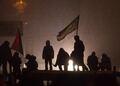 Вечер 21 января. Протестующие на крышах сгоревших автобусов в свете милицейского прожектора. Фото Юрия Тимофеева/Грани.Ру