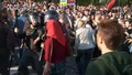 """Полицейский Антонов замахивается дубинкой на девушку. Гущин стоит в стороне. Кадр видеозаписи """"Nevex TV"""" из """"Болотного дела"""""""