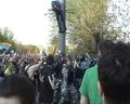 Омоновец не подпускает его, размахивая дубинкой. Справа бьют Луцкевича и других демонстрантов.